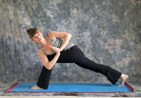 parivrtta: Young woman on yoga mat Yoga posture Parivrtta Parsvakonasana or Revolved Extended Side Angle pose with hands in prayer position against a grey background, facing left lit by diffused sunlight.
