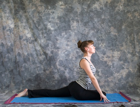 Young woman on yoga matdoing Yoga posture Salamba Kapotasana or Supported Pigeon Pose against a grey background in profile, facing right lit by diffused sunlight.