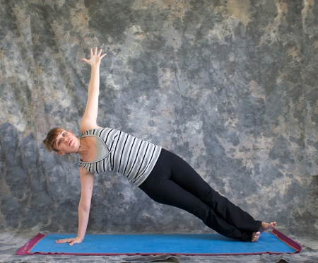 Young woman on yoga mat  doing Yoga posture Vasisthasana or side plank pose against a grey background front view, facing left lit by diffused sunlight. photo