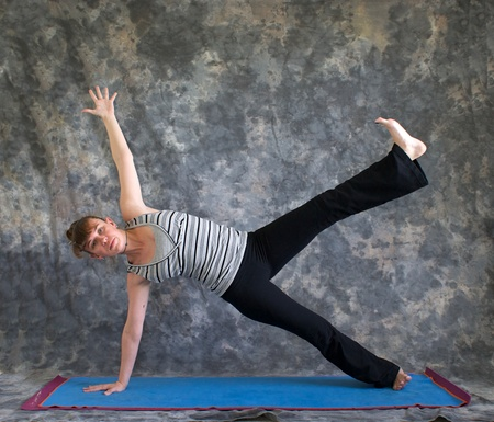 Young woman on yoga mat  doing Yoga posture Vasisthasana or side plank pose variation with arm and leg raised against a grey background front view, facing left lit by diffused sunlight. photo
