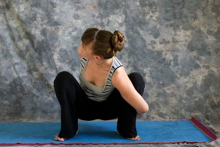 Young woman on yoga mat  doing Yoga posture bound Malasana or garland squat pose against a grey background in profile, facing left lit by diffused sunlight. photo