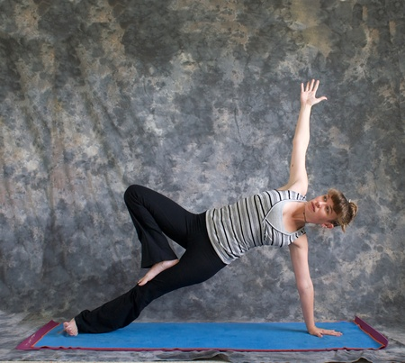 Young woman on yoga mat  doing Yoga posture Vasisthasana or side plank pose variation with arm raised and knee bent against a grey background front view, facing right lit by diffused sunlight. photo