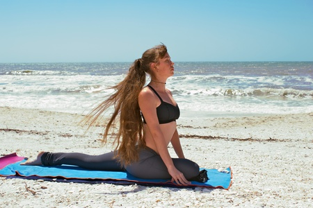 an athletic brown haired woman is doing yoga exercise woman doing yoga exercise on beach in Salamba Kapotasana or Supported Pigeon Pose on an empty beach at the gulf of mexico in bonita springs floridawith long hair blowing in wind Stock Photo