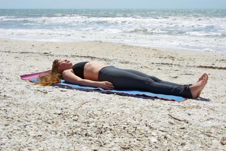 アスレチック、茶色の髪の女性はヨガ運動 Savasana を行うまたはボニータのメキシコ湾で空のビーチでの死体のポーズ スプリングス フロリダ。