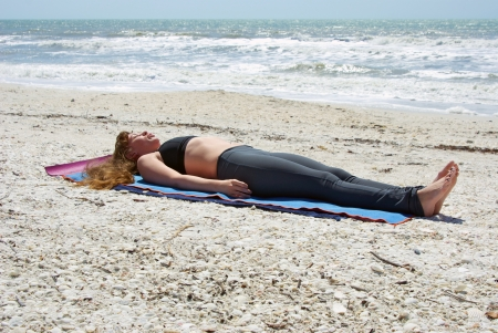 an athletic brown haired woman is doing yoga exercise Savasana or corpse pose on an empty beach at the gulf of mexico in bonita springs florida.