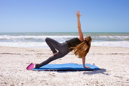 an athletic brown haired woman is doing yoga exercise  Vasisthasana or side plank pose on an empty beach at the gulf of mexico in bonita springs florida with long hair blowing in wind. photo