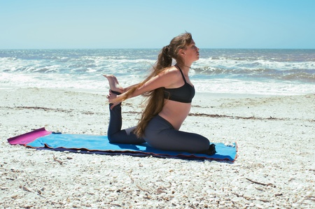 an athletic brown haired woman is doing yoga exercise woman doing yoga exercise on beach in Kapotasana or Pigeon Pose with both arms back and holding foot on an empty beach at the gulf of mexico in bonita springs florida with long hair blowing in wind