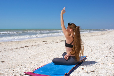 an athletic brown haired woman is doing yoga exercise bound half lotus or Ardha Padmasana with hand raised in om mudra position on an empty beach at the gulf of mexico in bonita springs florida with long hair blowing in wind photo