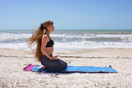 an athletic brown haired woman is doing yoga exercise on an empty beach Virasana or hero pose at the gulf of mexico in bonita springs florida with long hair blowing in wind