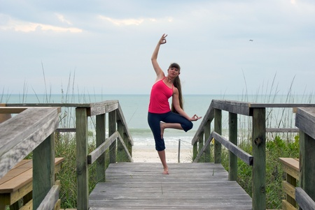 an athletic brown haired woman is doing yoga exercise dancing shiva tree pose on an empty boardwalk at the gulf of mexico in naples florida at sunset photo