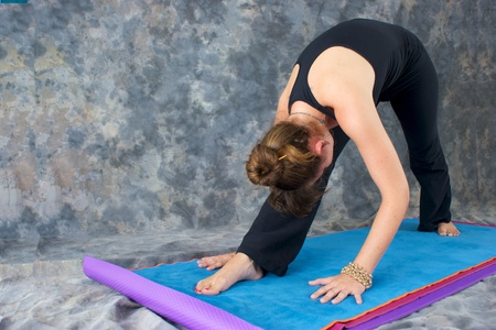 A brown haired caucasian woman is doing yoga exercise, Pyramid Pose or Parsvottonasana posture  on yoga mat in studio with mottled background. Stock Photo - 10001276