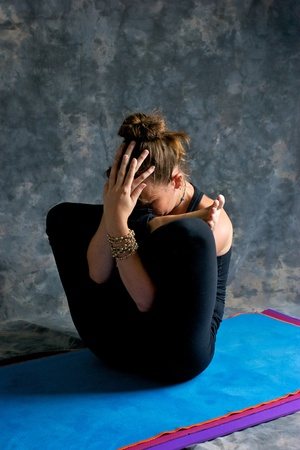 contortionist: A brown haired caucasian woman is doing yoga exercise, Womb Embryo Posture or Garbha Pindasana posture studio on yoga mat with grey mottled background. Stock Photo