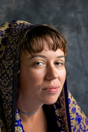 full lips: Portrait of a young woman with brown hair and bangs, big eyes and full lips looking at viewer.
