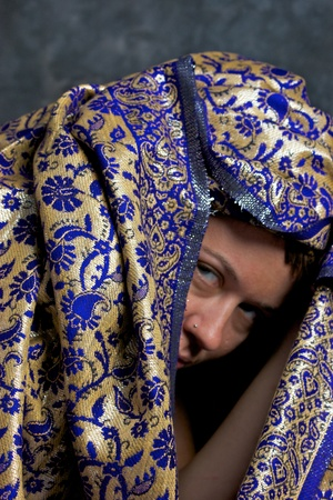 A woman is peering out from under an exotic blue and gold cloth and looking menacingly at the viewer. Фото со стока