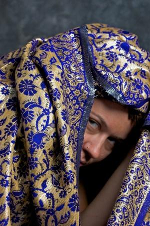 tissu or: Une femme regardant de dessous d'un tissu exotique bleu et or et en regardant mena�ante sur le spectateur.