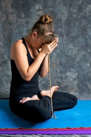 Studio portrait of beautiful young woman praying with beads, her eyes are closed and head bowed and her feet are in lotus position.