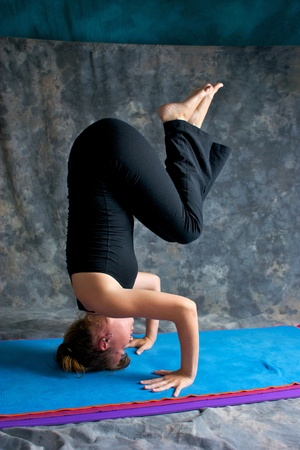 contortionist: A young woman with brown hair is doing advanced yoga asana  Sirsasana or Headstand.