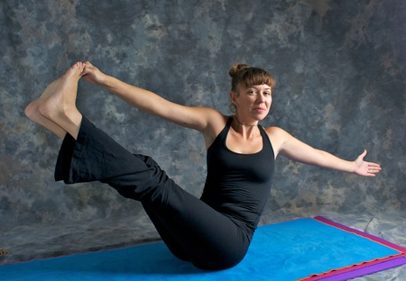 rotated: A brown haired caucasian woman is smiling doing yoga exercise, Navasana Pose or Rotated Boat posture  on yoga mat in studio with mottled background.