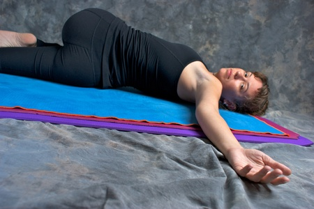 revolved: low angle view of brown haired caucasian woman is doing yoga exercise, Ardha Jathara Parivarttanasana Pose or Half Revolved Belly posture  on yoga mat in studio with mottled background. Looking at viewer with shallow depth of field.