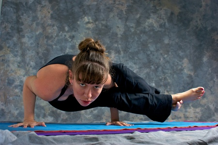 cursed: A brown haired caucasian woman is doing yoga exercise, Astavakrasana Pose or Ancient Sage Cursed with Crooked Limbs  posture  on yoga mat in studio with mottled background.  Stock Photo