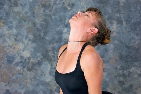 the neck: Una bella donna ha chiusi gli occhi e ha inclinato indietro come lei archi in postura cane di fronte al rialzo, vene possono essere visto sul collo, su uno sfondo chiazzato con spazio di copia. Archivio Fotografico