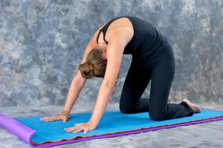 yogini: Young woman on yoga mat in  Yoga posture Marjaryasana or cat pose against a grey mottled background .