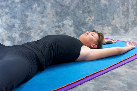 stretched out: an athletic brown haired woman is stretched out on yoga mat with hands above head in studio with a mottled grey background. Stock Photo