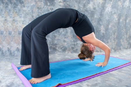 dhanurasana: an athletic brown haired woman is doing yoga exercise full wheel pose or Urdhva Dhanurasana also known as upward bow posture on yoga mat in studio with mottled background. Stock Photo