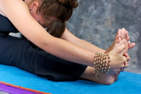 Close up of a womans hands and feet as she bends over in a yogic forward fold or Paschimottasana on yoga mat in studio wearing mala beads. Stock Photo