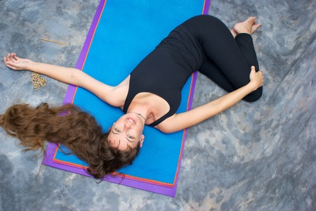 revolved: Seen from above, a brown haired caucasian woman doing yoga exercise, Ardha Jathara Parivarttanasana Pose or Half Revolved Belly posture  on yoga mat in studio with mottled background.