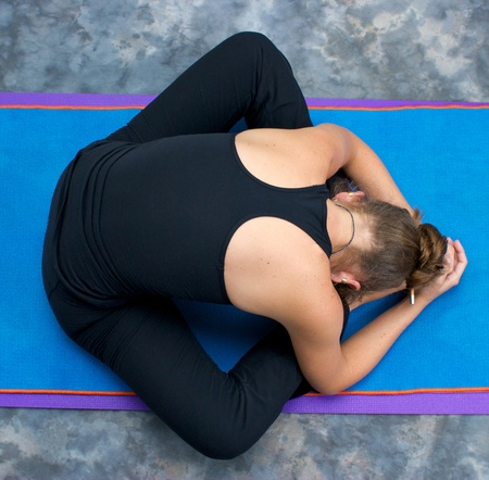 brown haired: Looking down on an athletic brown haired woman doing yoga exercise Bound Angle Forward Bend pose on yoga mat in studio with mottled background.