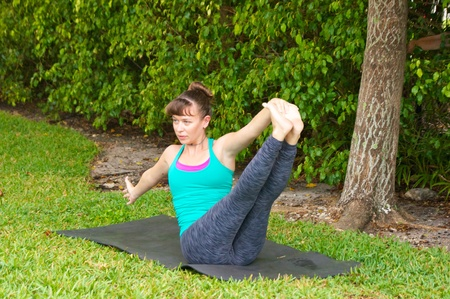 Young woman on yoga mat outdoors on the grass with trees in the  background in early morning light in Navasana variation or boat pose. photo