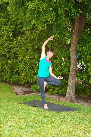 Young woman on yoga mat outdoors on the grass with trees in the  background in early morning light doing tree variation. photo