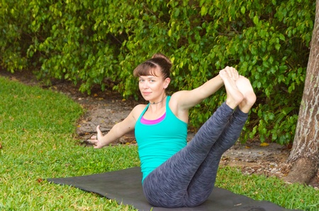 Young woman on yoga mat outdoors on the grass with trees in the  background in early morning light in Navasana variation or boat pose looking at viewer. photo