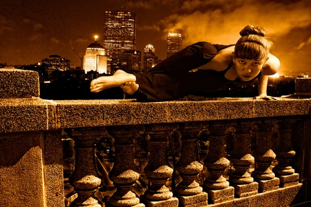 Female Yoga doing arm balance on top of skyscraper cement balustrade, boston skyline is in the distance behind her with smoke photo