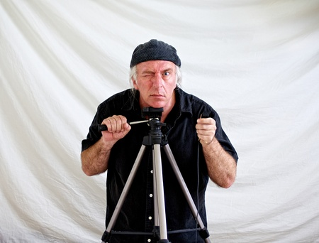 crazed: Crazed looking man resting head on tripod and holding shutter release in hand looking intently at viewer while other hand holds tilt arm of tripod.