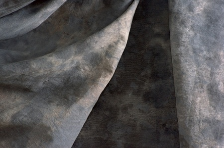 Close up  of a draped mottled grey backdrop cloth with folds in the fabric. Imagens