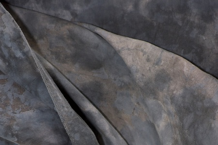 Close up  of a mottled grey backdrop cloth with folds in the fabric.