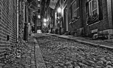 19th century: Black and white night image of an old 19th Century cobble stone road in Boston Massachusetts, Lit only by the gas lamps revealing the shuttered windows and brightly lit doorways of the rowhouses on Acorn Street.