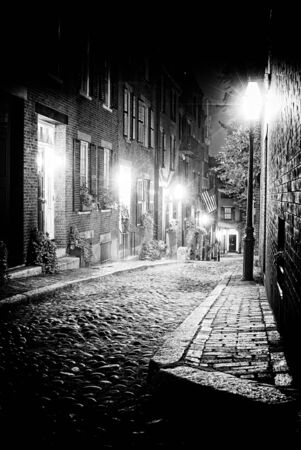 eerie: Black and white night image of an old 19th Century cobble stone road in Boston Massachusetts, Lit only by the gas lamps revealing the shuttered windows and brightly lit doorways of the rowhouses on Acorn Street.