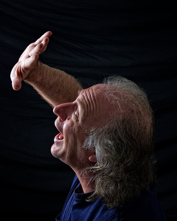 'hide out': A scared older man his his hand up in front of his face trying to hide and is screaming out in fear. Stock Photo