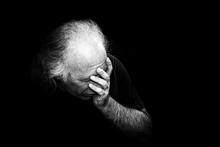 added: Gritty black and white image of older man holding head in despair, grain added to make more dramatic.