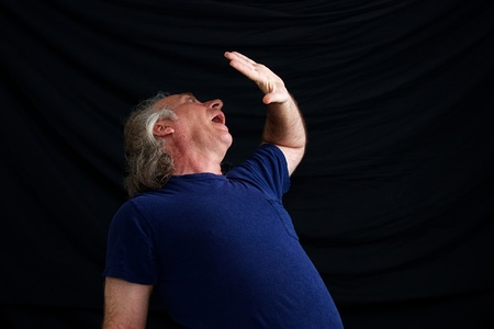 cowering: An older white man is cowering in fear and has hand up in front of face to protect him. Stock Photo