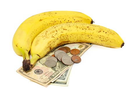 rising prices: Fresh ripe bananas on white with US currency, dollars and coins, as a concept for the rising prices of commodities, inflation, rising food costs, hunger. Stock Photo