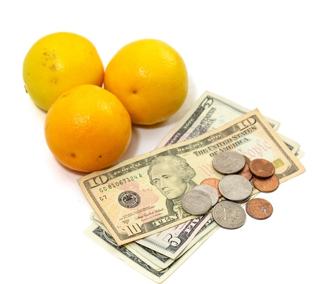 Fresh oranges on white with US currency, dollars and coins, as a concept for the rising prices of commodities, inflation, rising food costs, hunger.