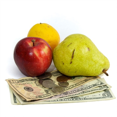 commodities: Fresh fruit on white with US currency, dollars and coins, as a concept for the rising costs of commodities, inflation, rising food costs, hunger. Stock Photo