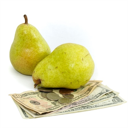 commodities: Fresh pears on white with US currency, dollars and coins, as a concept for the rising costs of commodities, inflation, rising food costs, hunger.