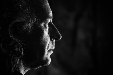 male profile: Black and white profile portrait of older white male with side lighting.