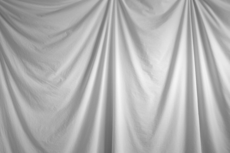 draped cloth: a white fabric draped backdrop hanging indoors.