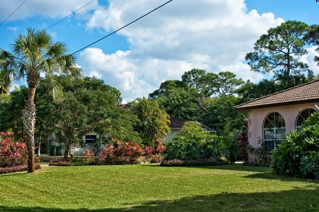 View of a typical southern florida neighborhood in early afternoon, showing houses, trees, and lawn  Stock Photo